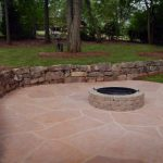 firepit with stone wall in backyard