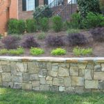 stone retaining wall and shrubs