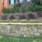 stone retaining wall and shrubs