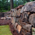 stone wall and pinestraw