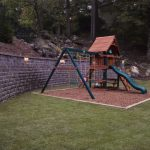 playground in backyard with stone wall