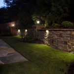 stone wall with grass and outdoor lighting