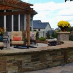 firepit with stone wall and flowers